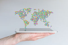 World map floating above a modern smart phone or tablet. Hand holding mobile device in front of grey background. Royalty Free Stock Images