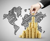 World map. Hand building coins chart and world map Stock Photo