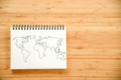 World map outline on notebook Royalty Free Stock Image