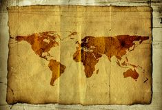 World map on parchment. The world map brown grungy background with scratches marks and spills printed on  parchment Royalty Free Stock Photo