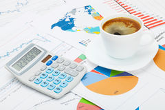 World map and some charts under coffee cup and calculator Royalty Free Stock Photo