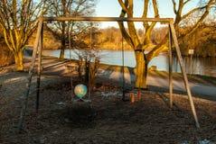 The world may swing. Globe put on a playground swing, representing a fine balance stock photo