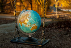 The world may swing. Globe put on a playground swing, representing a fine balance royalty free stock photography