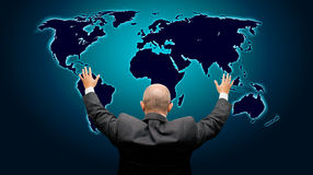 The world is mine - back version. Business man with hands in the air in front of a blue glowing world map - high details royalty free stock photo
