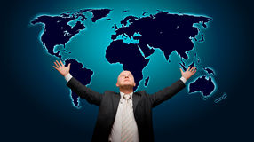 The world is mine - front version. Business man with hands in the air in front of a blue glowing world map - high details stock images