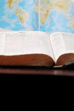World missions. Bible open to the Book of Acts (the book that describes spreading the Gospel to the World) and a world map in the background. World missions stock photography