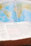 World missions. Bible open to the Book of Acts (the book that describes spreading the Gospel to the World) and a world map in the background. World missions royalty free stock image