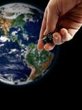Dice and the earth. Gesturing hand throwing dice and the earth on the background Royalty Free Stock Photography