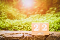 "World Mother Earth day background concept. Wooden calendar with date ""22 april"" with green nature background. International World Mother Earth day royalty free stock photos"