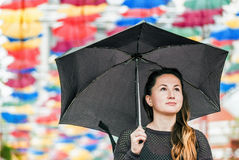 The world is much brighter than you could think of it. Interesting photo of a young woman in a dark (almost black clothes) with black umbrella. Background is royalty free stock image
