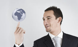 The world on my finger. Young businessman spinning (holding) the world (globe) in his finger Stock Photo