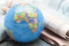 World news. Picture of a terrestrial globe over some newspapers Royalty Free Stock Photo