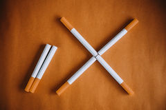 World No Tobacco Day : Cigarette put on brown table showing sign no smoking Royalty Free Stock Images