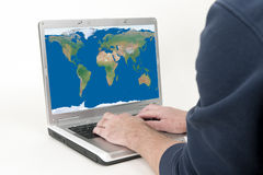World at Our Finger Tips. Laptop Computer and World Map Representing the World At Our Finger Tips Stock Images