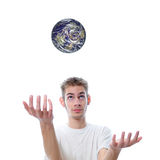 The World Is In Our Hands. Young adult white Caucasian man throws the world up in the air Stock Images