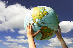 World in the our hands. Globe in the child's hands on the cloudy sky background Stock Images
