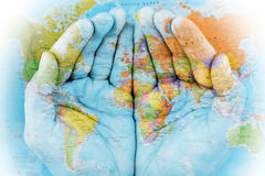 The world in our hands. Map of the world painted on hands royalty free stock photography