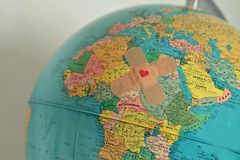 World with plaster with heart - Solidarity and aid to countries Royalty Free Stock Image