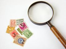 World postage stamps and magnifying glass Stock Image
