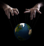 World puppet master. Hand with cords manipulate the destiny of the world Royalty Free Stock Photo
