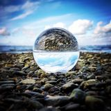 The world  in reverse. Glass ball photography on the West Coast of Canada.  Beautiful reflection turning the sky into beach Royalty Free Stock Image