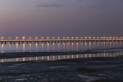 The world's longest bridge - hangzhou bay bridge, through the wetlands of hangzhou bay. Sunset, two rows of lighted on the bridge, the reflection in the water Royalty Free Stock Images