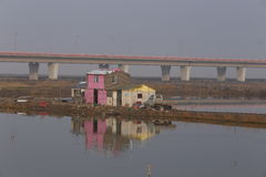 Is the world's longest bridge next to the fish pond, pond beside the pink simple house  Stock Image
