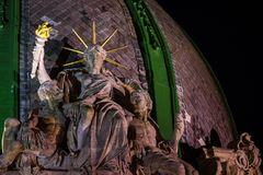 The world`s only sitting Statue of Liberty at night time. Lviv woman Liberty gently embraces two men. Ukraine, Lviv, 1891 stock photo