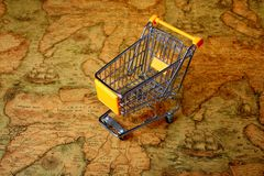 World shopping cart globalisation. Shopping cart on ancient world map,global shopping concepts royalty free stock image