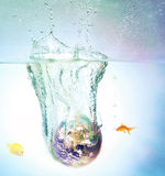 World Sinking in Water. A globe sinking in water with bubbles Stock Photos