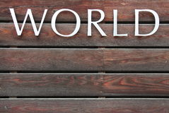 WORLD text on brown background. WORLD text on brown wood background Royalty Free Stock Images