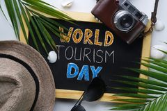 World Tourism Day Typography. Sunglasses, Fedora Hat, Palm Leaf, Camera, Sea Shells and Blackboard royalty free stock photography