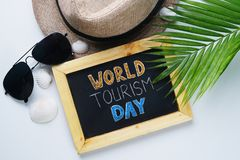 World Tourism Day Typography. Sunglasses, Fedora Hat, Palm Leaf, Sea Shells Background. stock photography