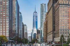 World Trade Center fra le costruzioni sopra la strada affollata, osservata dal parco di batteria in Lower Manhattan fotografia stock libera da diritti