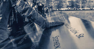World Trade Center Memorial at Ground Zero, Manhattan. A girl, putting his hand on the bronze parapet. Stock Photography