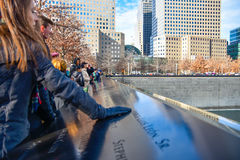 World Trade Center Memorial at Ground Zero, Manhattan. A girl, putting his hand on the bronze parapet. Royalty Free Stock Photos
