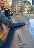 World Trade Center Memorial at Ground Zero, Manhattan. A girl, putting his hand on the bronze parapet. Royalty Free Stock Image