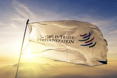 World Trade Organization WTO flag textile cloth fabric waving on the top sunrise mist fog. Beautiful royalty free stock images