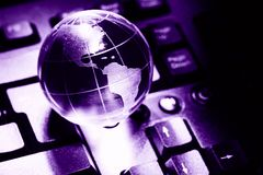 World transparent globe earth on computer keyboard. Global communications business concept. Ultraviolet colored Image. Color of th. E year - 2018 Royalty Free Stock Photos