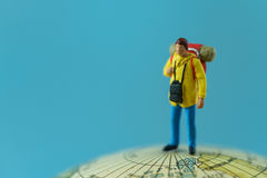 World Travel concept as a miniature figure with backpack standing on the globe with blue background and copy space.  royalty free stock photo