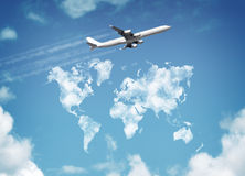 World travel. Passanger airplane flying above sky with clouds in shape of world map concept for travel and vacations royalty free stock photo