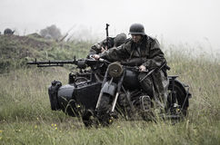 World War 2 scene. PEREVOZ VILLAGE, RUSSIA - JUNE 26, 2011: Heavily armed German motorcycle emerges from Russian army during historical reenactment of 1941 WWII Royalty Free Stock Image