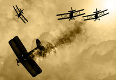 World War 1 aircraft scene. Vintage world war one biplanes and triplanes engaged in a dog fight  in a cloudy sky. One had success in shooting down the enemy Royalty Free Stock Photo