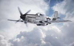 World War II era fighter flies among clouds and blue sky Stock Images