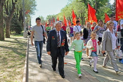 World War II veteran accompanied by relatives on Victory Day celebration in Volgograd. Volgograd, Russia - May 9, 2013: World War II veteran accompanied by Royalty Free Stock Photography