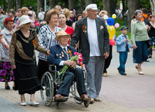 World War II veteran in a wheelchair and accompanied by relatives on Victory Day celebration on the Avenue of Heroes in Volgograd Royalty Free Stock Images