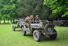 World War 2 Jeep with men dressed as World War 2 Soldiers, towing Gun. Stock Image