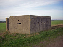 World War Two Pillbox. World War Two concrete pillbox on the east coast of Yorkshire, England. Rear entrance and loopholes visible. Surrounded by grass. Blue sky Royalty Free Stock Photo