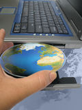 World at your fingertips. Hand inserting the world into a computer Royalty Free Stock Images