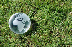 World In Your Garden. A small glass globe laying on a grass background Royalty Free Stock Photo